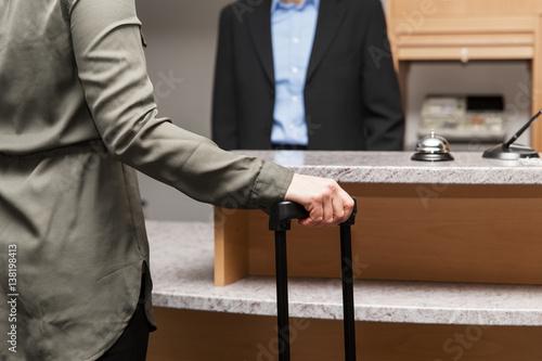 Plakat Kobieta stoi w recepcji hotelu, gość odprawia