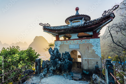 Fotobehang Guilin Chinese style architecture and sunrise karst mountains view in Yangshuo, Guangxi Province, China