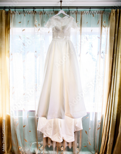 7c7ee3598b2 Long wedding dress with lace top hangs before window with beige curtains