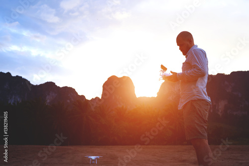 Fototapety, obrazy: Silhouette of a young man is holding remote control of a drone, while is standing against rock mountains in summer evening. Male traveler is using quadcopter during his unforgettable trip in Thailand