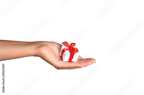 Fotomural  Woman's hand with a small white gift box with bow isolated on white background