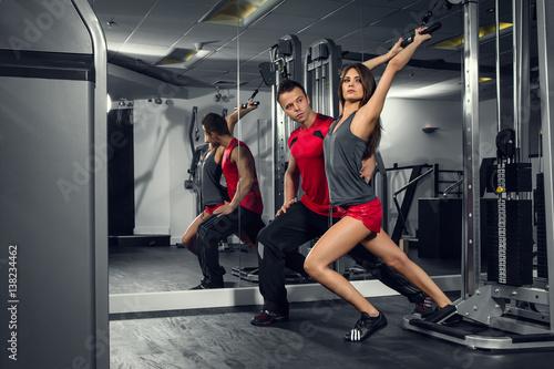 Obraz fitness, siłownia, kobieta, sportowiec - Młoda dziewczyna trenuje na siłowni z trenerem personalnym - fototapety do salonu