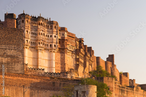 Fortification Details of Jodhpur fort at sunset. The majestic fort perched on top dominating the blue town. Scenic travel destination and famous tourist attraction in Rajasthan, India.