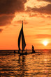 Sailing boats at sunset on a tropical ocean