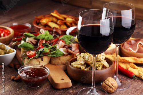 Italian antipasti wine snacks set. Cheese variety, Mediterranean olives, pickles, Prosciutto di Parma, tomatoes, artichokes and wine in glasses - 138246484