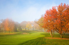 Misty Autumn Morning. Morning Mist And Sun Light. Fog Over Golf Course During Beautiful Fall Sunrise. Colorful Autumn Trees On A Bright Green Lawn. Horizontal Composition.