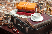 Old Suitcase With Old Books And Cup Of Tea On Brown Background