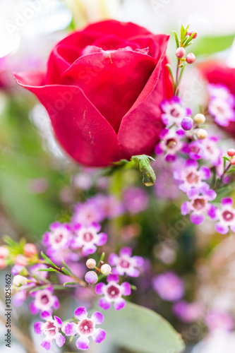 Closeup of red rose bouquet with tiny purple flowers