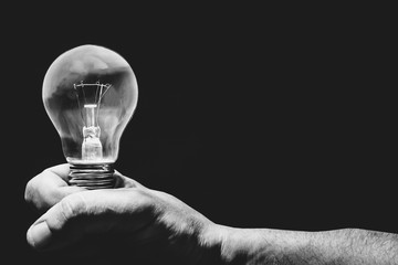 Black and white photo. Hand holding light bulb on black background.