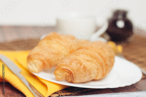 Photo Stands Coffee beans two croissants on a plate, yellow napkin