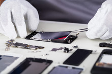 Repairman Disassembling Smartphone With Tweezers