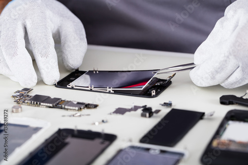 Repairman Disassembling Smartphone With Tweezers