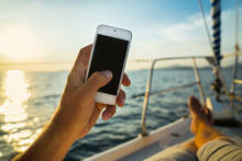 Summer Leisure. Rest On A Yacht With A Phone In His Hand. Man Lying On The Deck And Enjoy Your Smartphone. The Guy Doing The Photo Feet On The Background Seascape And Yachts.