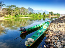 Lao Traditional Boats On The Shore Of A Mountain River