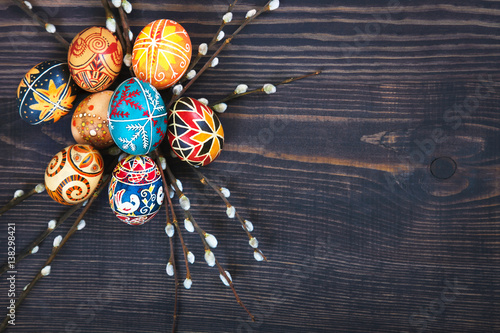 Photo  Easter eggs with willow twigs on a wooden plank table.