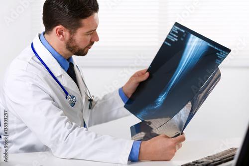 Fotografía  Male doctor looking at patients x-ray