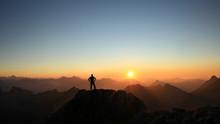 Man Reaching Summit Enjoying Freedom And Looking Towards Mountains Sunset.