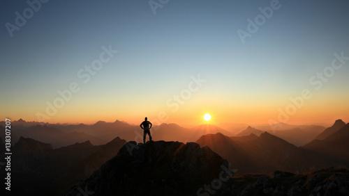 Fototapeta Man reaching summit enjoying freedom and looking towards mountains sunset. obraz na płótnie