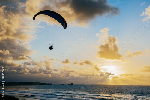 Poster Luchtsport Silhouette of person flying on the parachute over the sea in sunset lights.