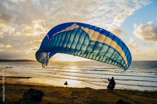Foto op Canvas Luchtsport Silhouette of person flying on the parachute over the sea in sunset lights.