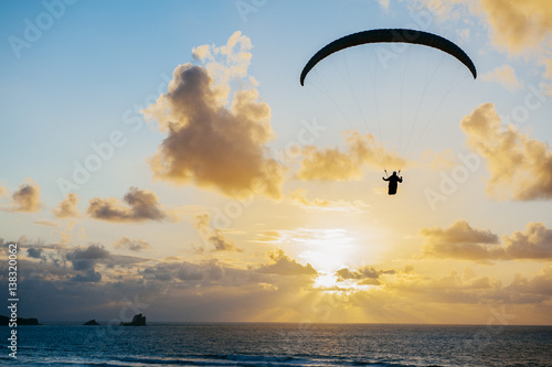 Spoed Fotobehang Luchtsport Silhouette of person flying on the parachute over the sea in sunset lights.