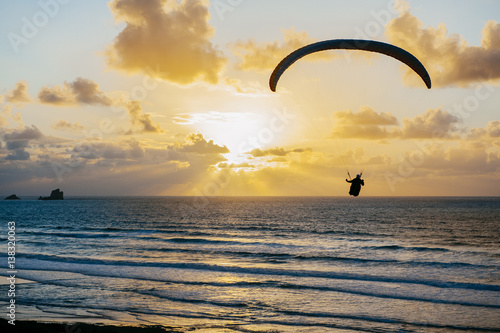 Foto op Aluminium Luchtsport Silhouette of person flying on the parachute over the sea in sunset lights.