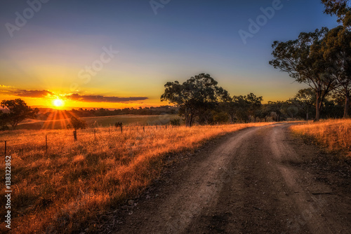 Poster Chocoladebruin Countryside landscape with rural dirt road at sunset in Australia