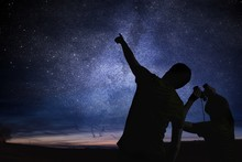 Silhouettes Of People Observing Stars In Night Sky. Astronomy Concept.
