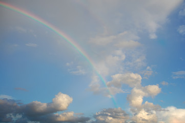 clouds with a rainbow. Multicoloured curved strip in the firmament, as a consequence of the refraction of sunlight in raindrops.