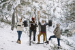 A group of people posing with barbels in the winter forest. Horizontal outdoors shot.