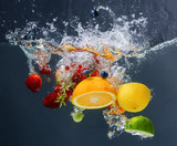 Different fruits and berries falling in water on dark background