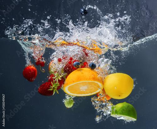 Fototapeta Different fruits and berries falling in water on dark background obraz na płótnie