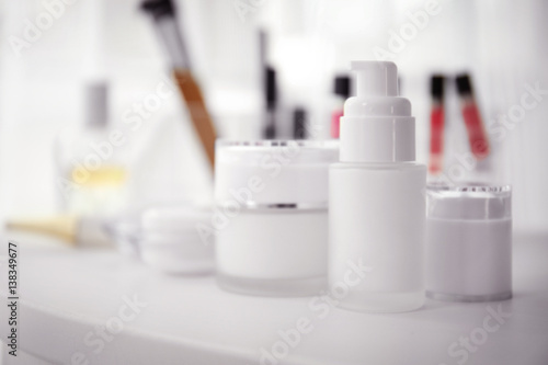 Fotografie, Obraz  Bottle and jars of cream on white table against blurred background, close up vie