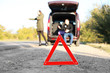 Red warning triangle on asphalt road. Couple catching car on road