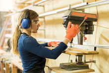 Woman Using A Drill Press For ...