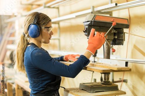 Fotografia  Woman using a drill press for work