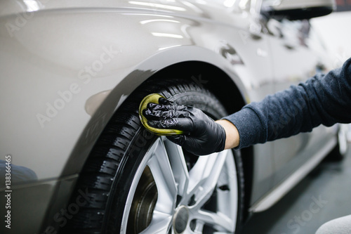 Zdjęcie XXL Człowiek czyszczenia samochodu z tkaniny z mikrofibry, samochód szczegółowo (lub valeting) koncepcja. Selektywna ostrość.