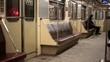 one person riding in a subway car, returning from work in the evening