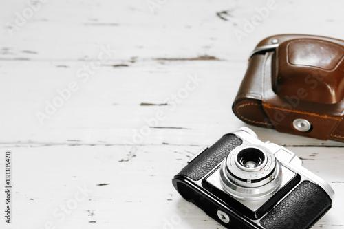 Stampe  Old film camera in brown vintage case  on white wood background