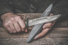 Man's Hands Sharpening Old Knife On The Wooden Table. Dark, Vintage Atmosphere.