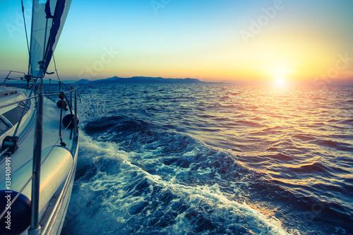 Łódź w regatach żeglarskich podczas zachodu słońca.