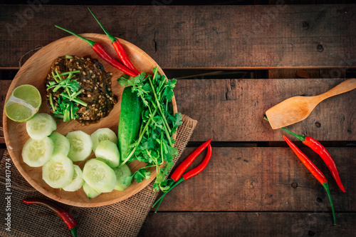 Vintage style Thai traditional food Nam Prik Num (Northern Thai Green Chilli Dip) on top and wooden background wallpaper