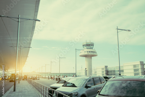 Poster Aeroport Parking lot and road near modern contemporary airport terminal in front of air traffic control tower, with many passengers and staff passing in distance, Barcelona, Spain