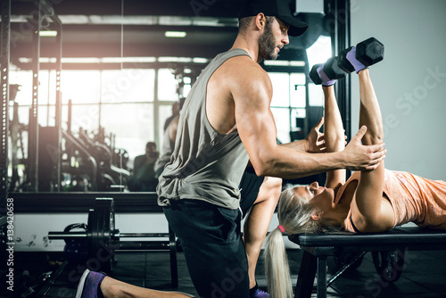 Female dumbbell chest press with help of personal trainer