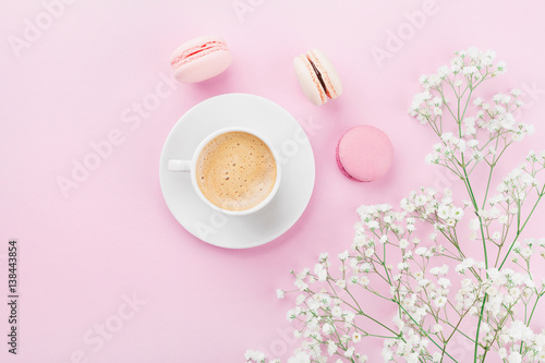 Foto op Canvas Bloemen Morning cup of coffee, cake macaron and flowers on pink table top view in flat lay style. Beautiful breakfast for woman.