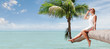 view of nice young lady sitting on palm on tropical beach.