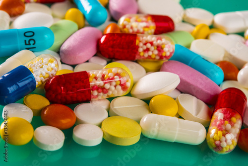 Poster Confiserie Multicolored pills and tablets on green background