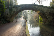 A Couple Walk Across A Solid Stone Hump Back Victorian Bridge As The Golden Wintry Morning Sun Rays Break Through The Trees And Highlight The Mist Rising From The River