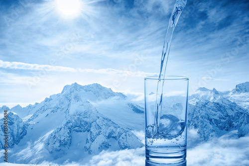 Foto auf Gartenposter Gebirge beautiful background of pouring blue water in transparent glass over winter landscape of mountains higher than clouds, close up