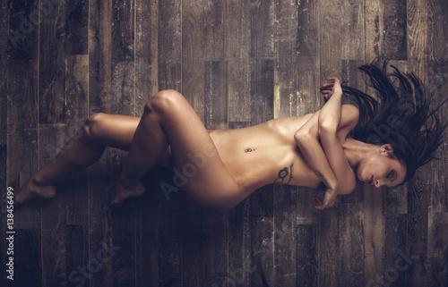 Zdjęcie XXL Młoda naga kobieta kłaść na drewnianej podłoga